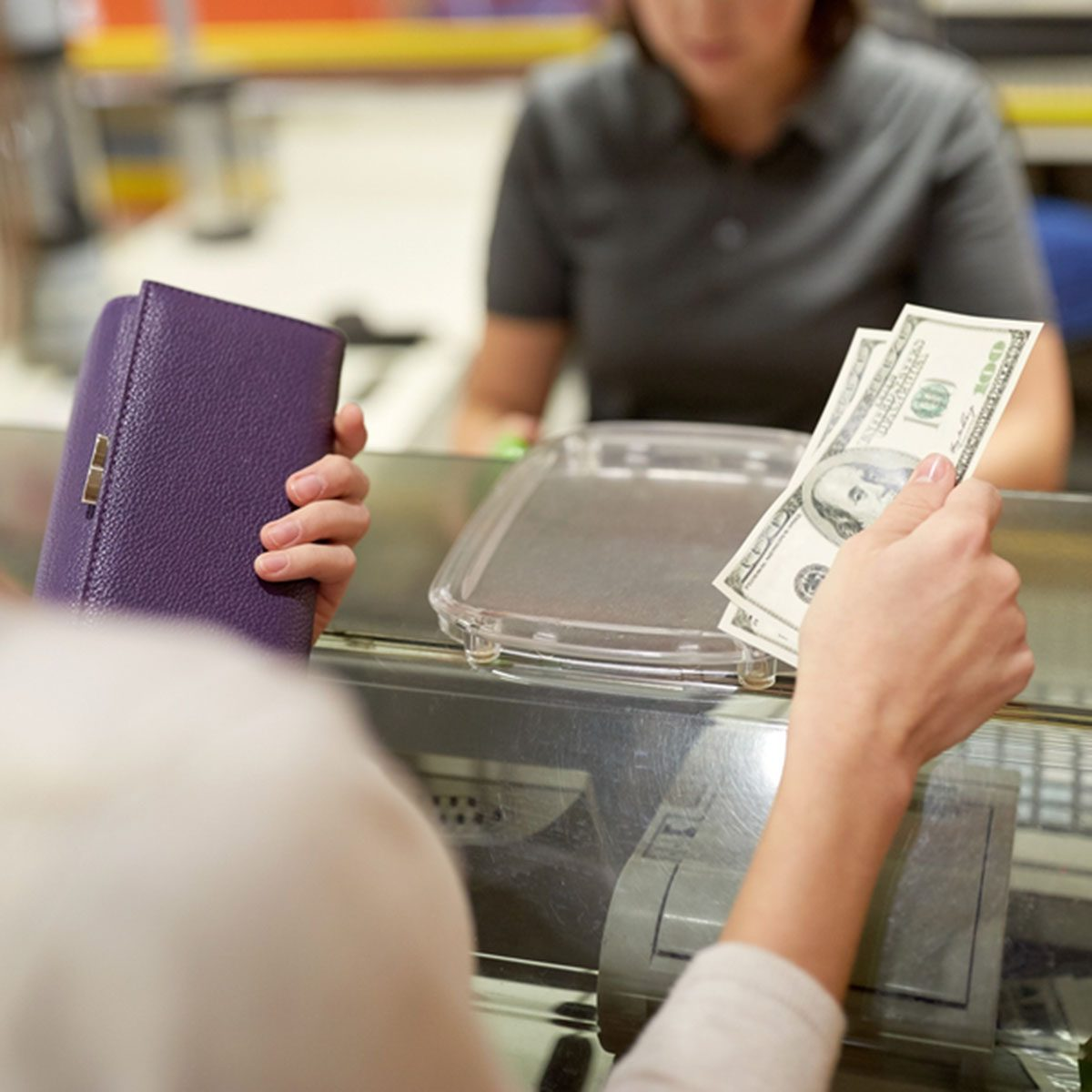 Woman paying money and cashier at store cash register