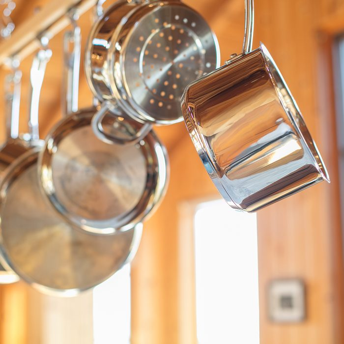 Pots and Pans hanging in Kitchen from wood rack: Stainless steel