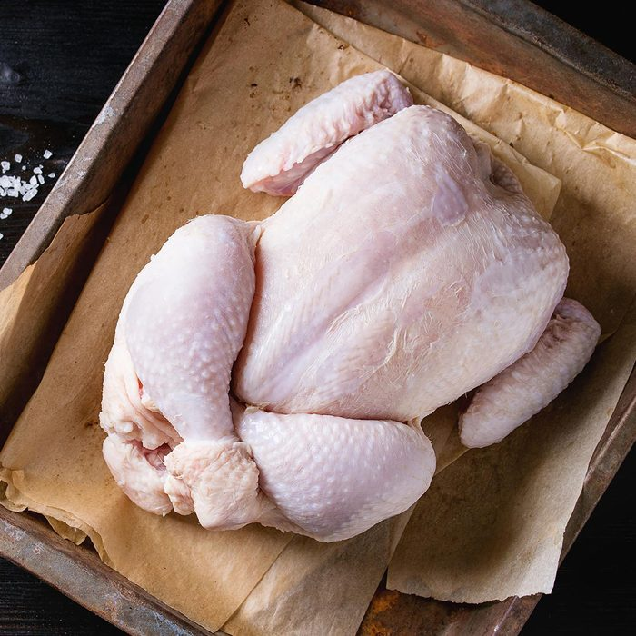 Raw organic uncooked whole chicken with salt and pepper on backing paper in old oven tray over black burnt wooden background