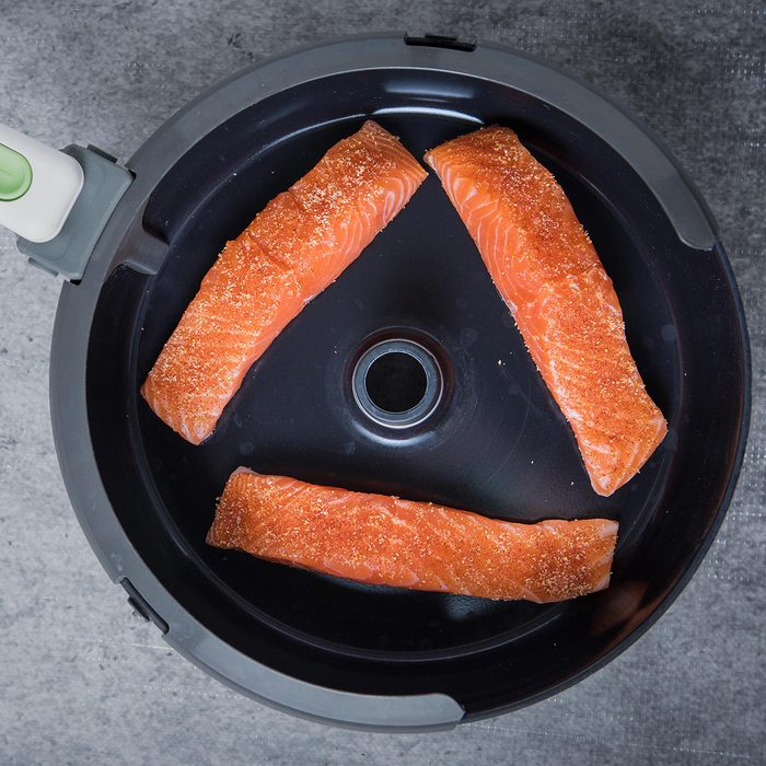 Three pieces of raw salmon in the air fryer at the center with a grey background.