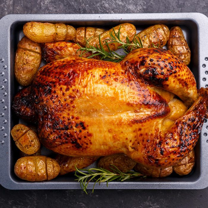 Roasted chicken and potatoes on black slate stone background