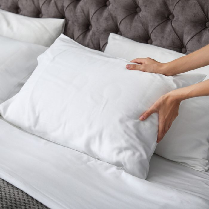 Young woman plumping white pillow on bed, closeup; Shutterstock ID 1149647606; Job (TFH, TOH, RD, BNB, CWM, CM): Taste of Home