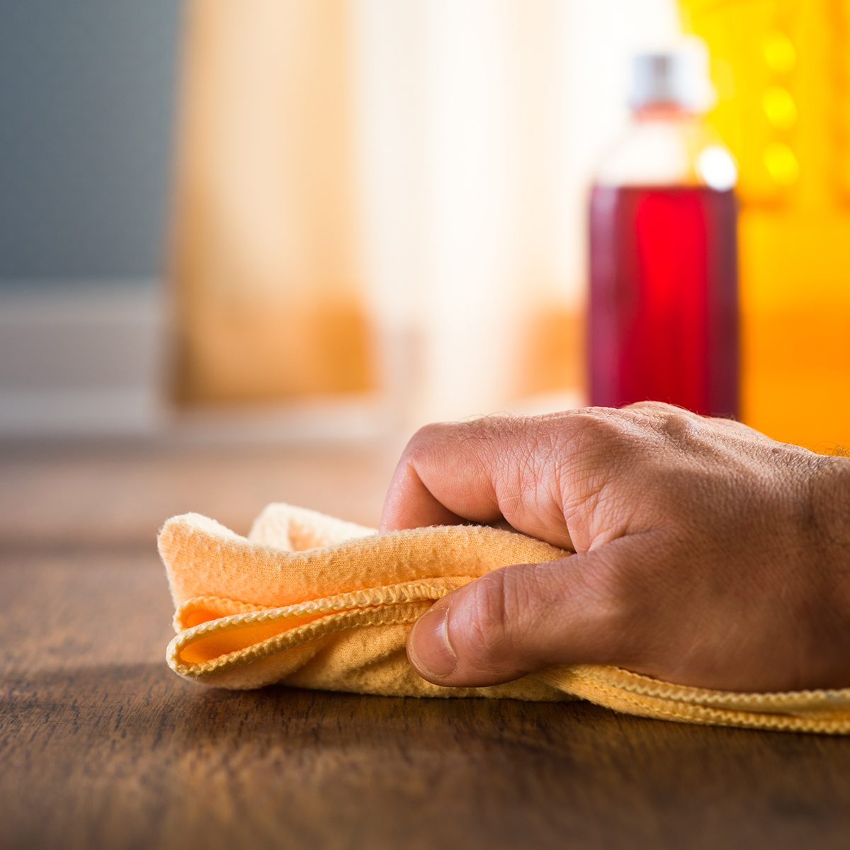Male hand applying wood care products and cleaners on hardwood floor surface.; Shutterstock ID 221628484