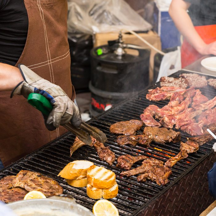 Person barbecuing meat at a catered event with a close up view of the chefs hands and meat cooking on the grill over a fire; Shutterstock ID 301829375; Job (TFH, TOH, RD, BNB, CWM, CM): Taste of Home