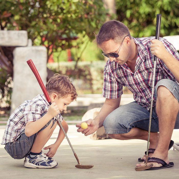 Sharing with golf experience. Cheerful young man teaching his son to play mini golf at the day time. Concept of friendly family.; Shutterstock ID 387900190; Job (TFH, TOH, RD, BNB, CWM, CM): Taste of Home