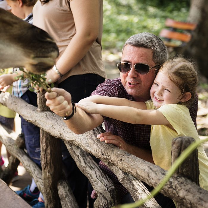Caucasian dad and daughter feeding the giraffe at the zoo; Shutterstock ID 663979918; Job (TFH, TOH, RD, BNB, CWM, CM): Taste of Home