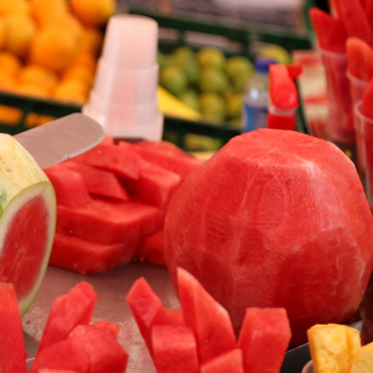 Man cuts the watermelon with a knife to prepare the fruit salad for sale