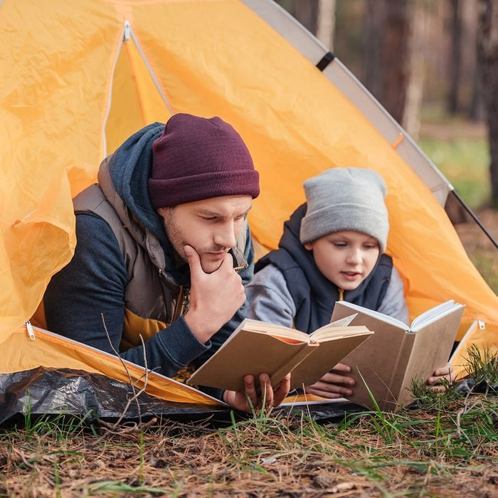 father and son reading books while lying together in tent; Shutterstock ID 740626120; Job (TFH, TOH, RD, BNB, CWM, CM): Taste of Home