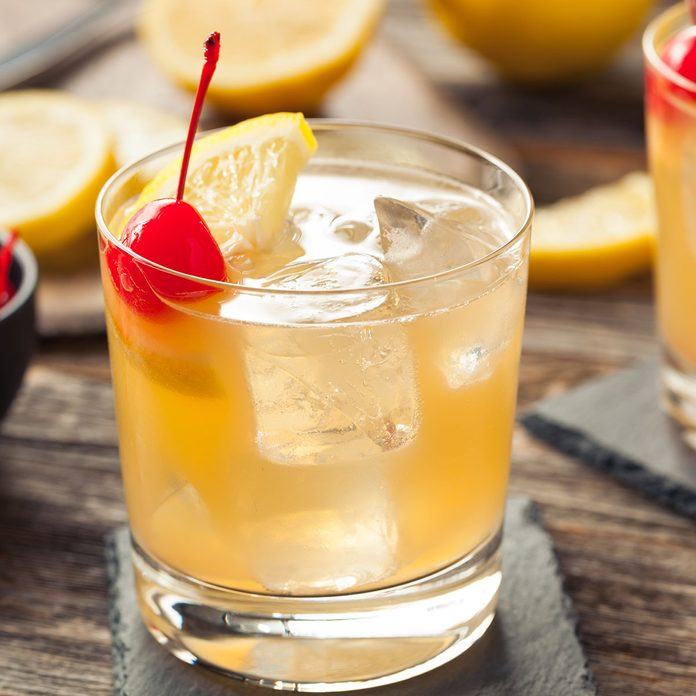 Homemade Whiskey Sour Cocktail Drink with a Cherry Lemon