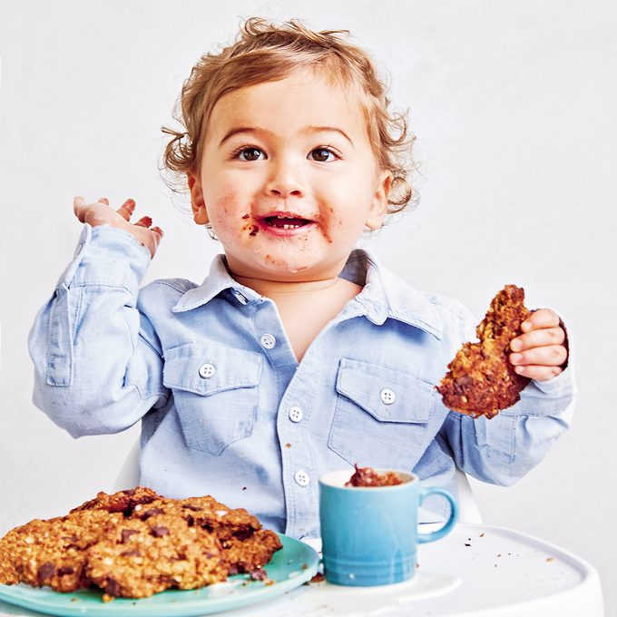 Young child messily eating breakfast cookies and smiling