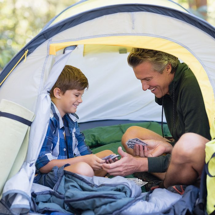 Happy father and son sitting inside tent while hiking in forest