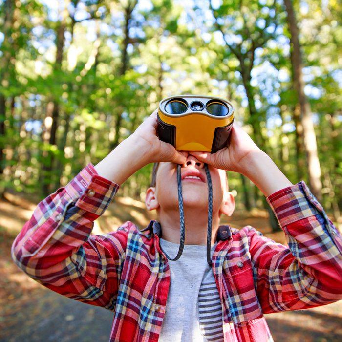 Boy looks up through binoculars.