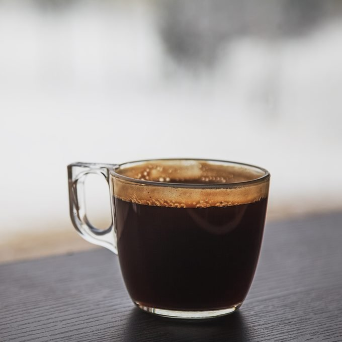 Transparent cup of coffee placed on dark brown laminated wooden surface in front of a window
