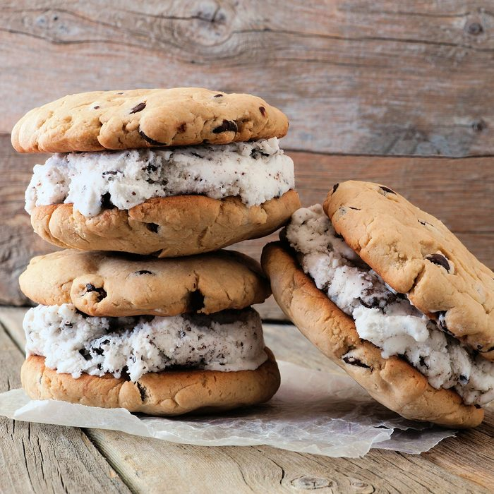 Homemade chocolate chip cookie ice cream sandwiches against a rustic wood background