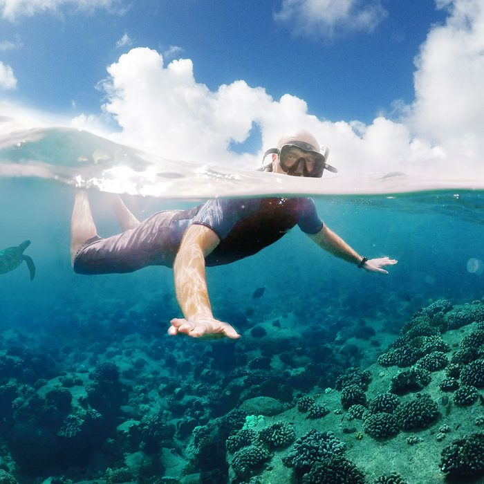 Snorkeling off of a boat in Hawaii with a split perspective of above the water and below it