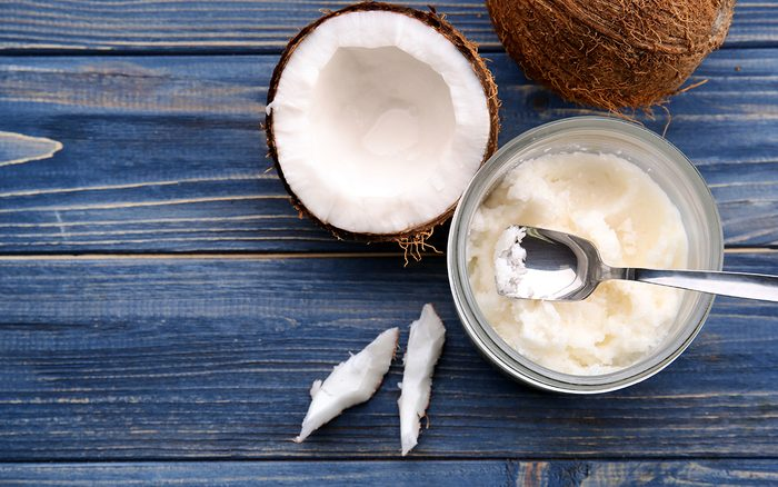 Opened glass jar with fresh coconut oil on wooden background