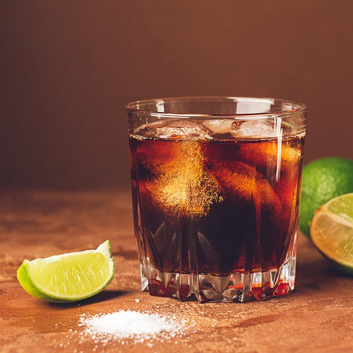 Cold cocktail drink with ice and pieces of juicy lime in a glass on a dark brown background.