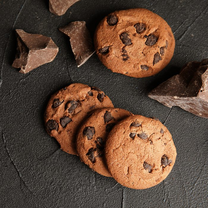 Tasty chocolate chip cookies on dark background, flat lay.