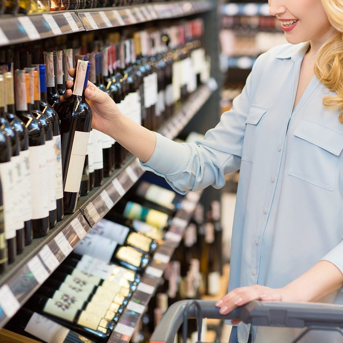 Cropped shot of a beautiful happy woman shopping at the supermarket walking with a shopping cart taking wine bottle from a shelf
