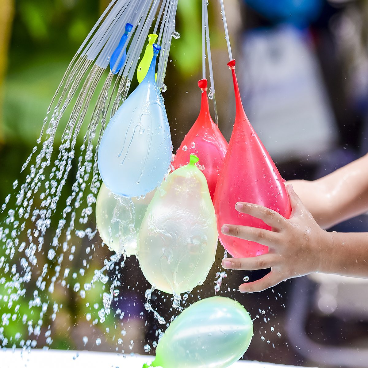 children holding colorful water balloons on his hand.