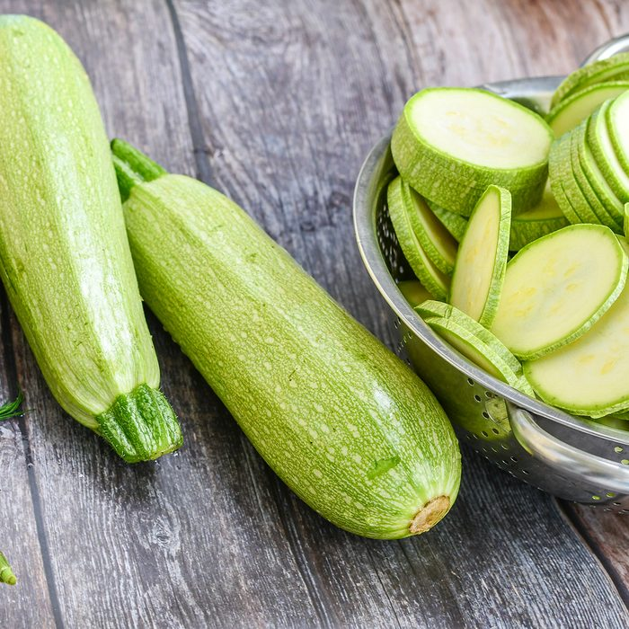 Fresh sliced raw bio zucchini and dill on wooden background.