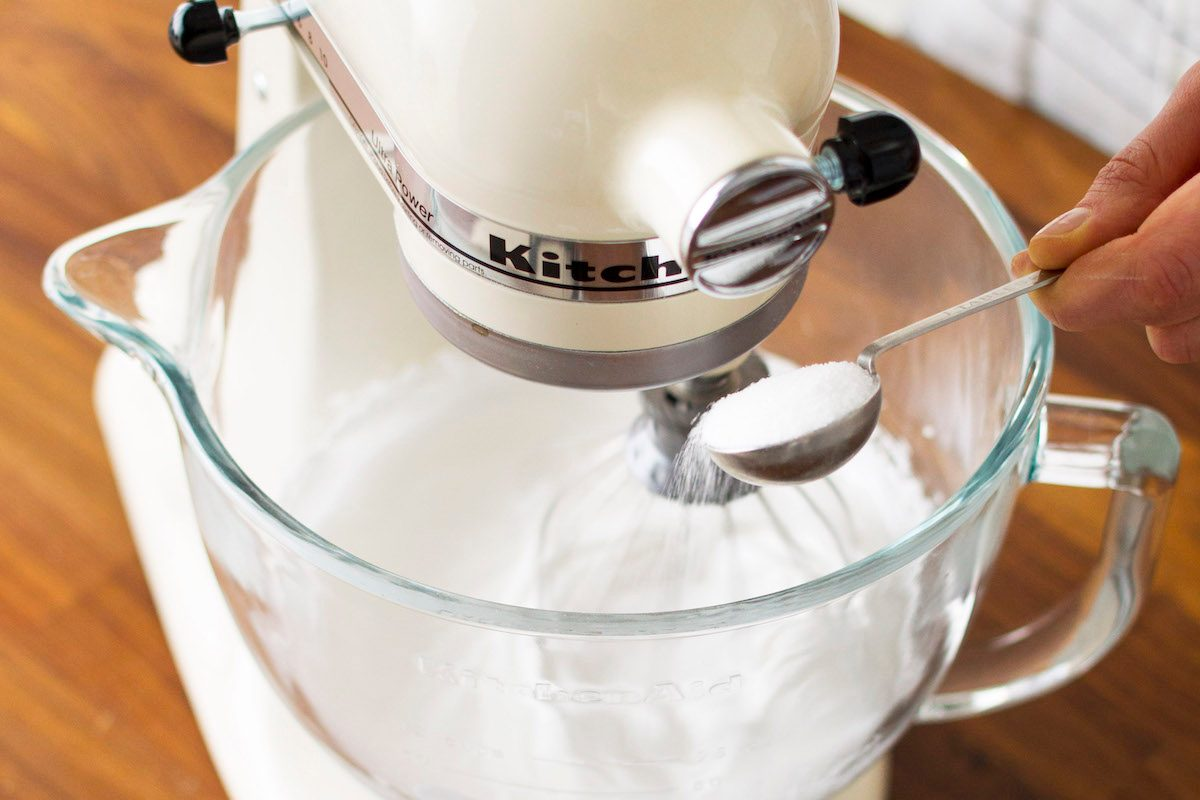 A close-up of someone adding sugar to the bowl of a stand mixer as they make homemade meringue.