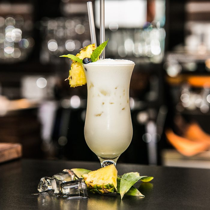 Pina colada cocktail with ice in the bar background.
