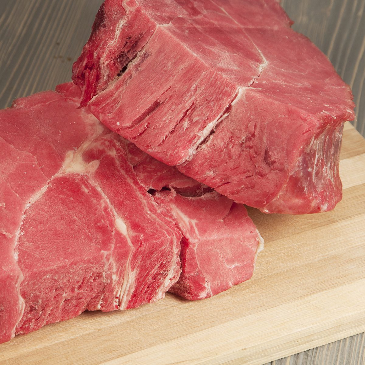 Two pieces of frozen beef on a board; Shutterstock ID 177201707; Job (TFH, TOH, RD, BNB, CWM, CM): TOH
