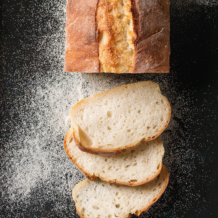 Sliced homemade white wheat bread with wheat flour on old black oven tray as background.