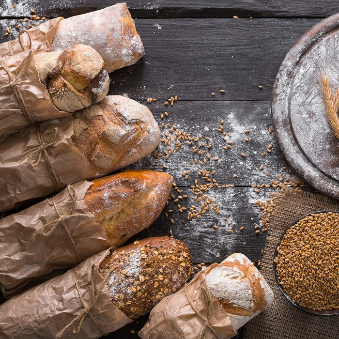 Bread background. Brown and white whole grain loaves wrapped in kraft paper composition on rustic dark wood