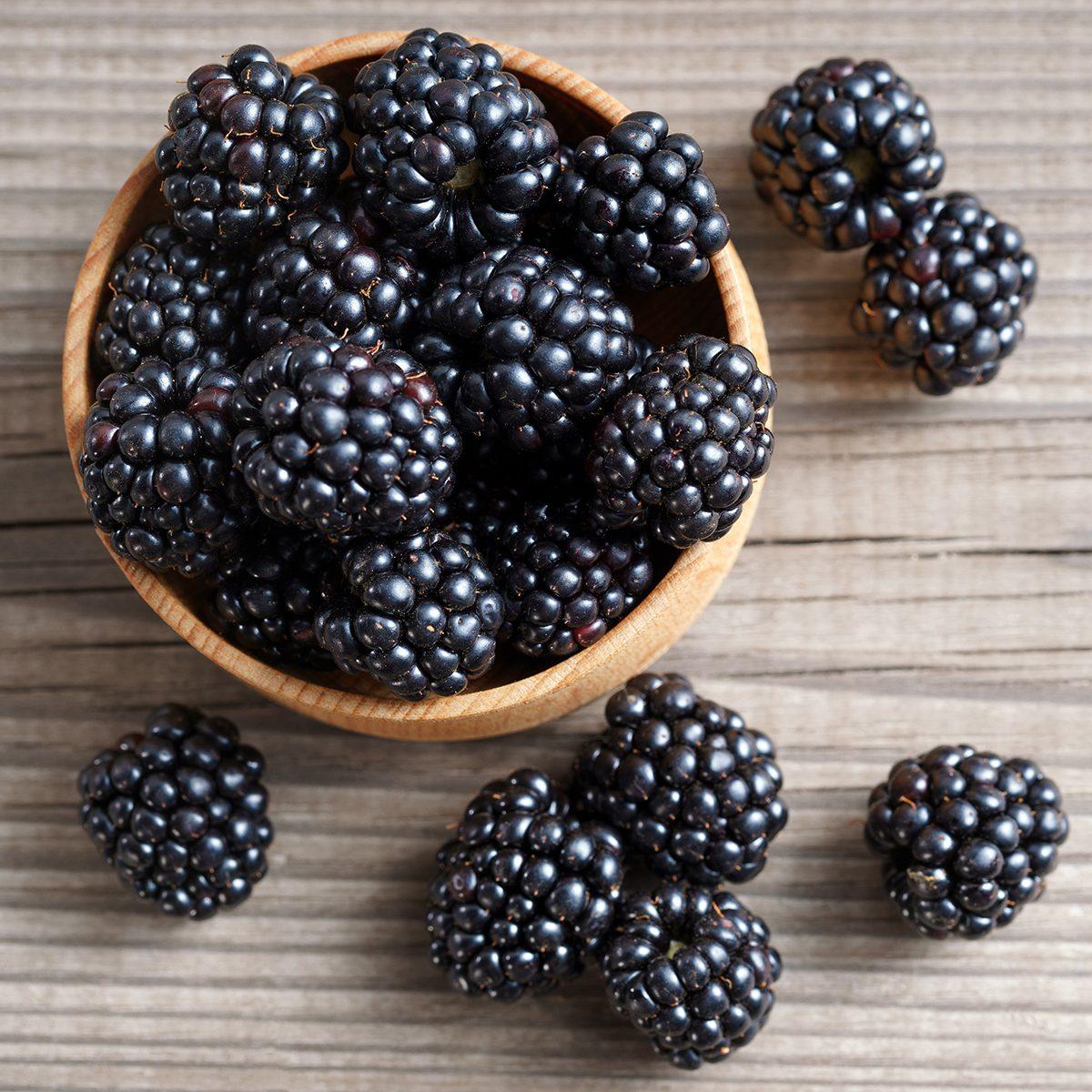 Deluxe blackberries in bowl on wooden background.