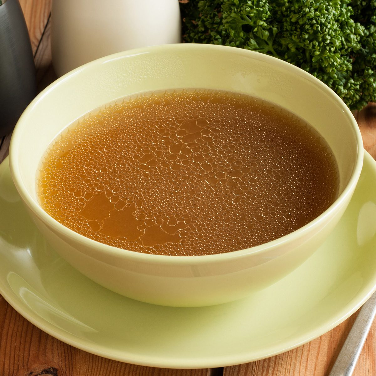 Bone broth made from beef, served in a green soup bowl