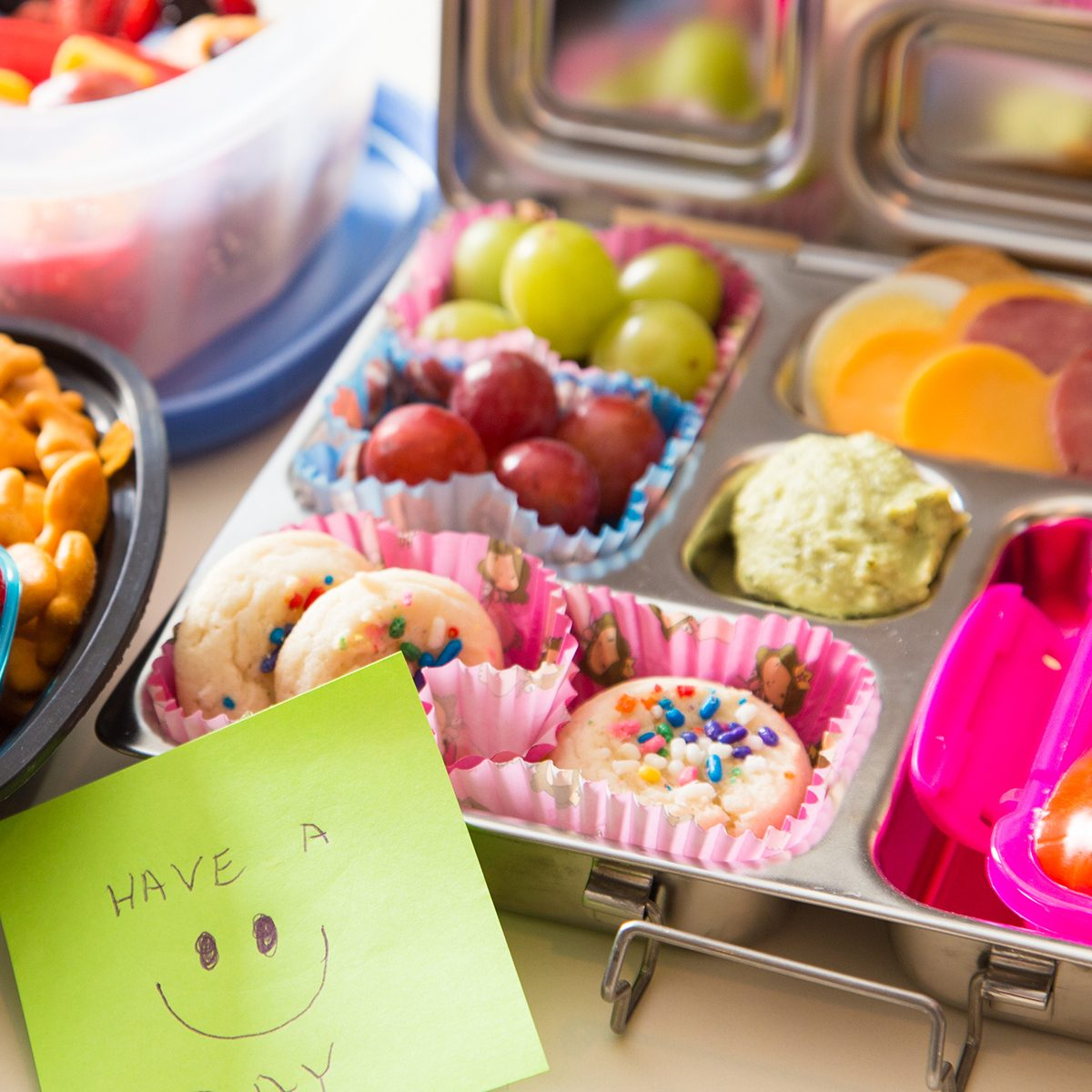 Mom packs a happy note of encouragement with a colorful Bento box lunch packed with healthy fruits, veggies and snacks