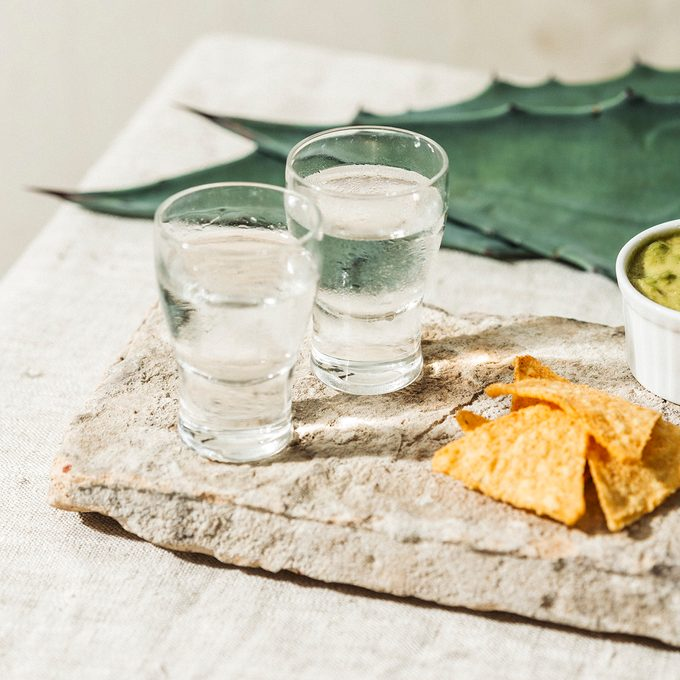 Mezcal or Mescal is a Mexican distilled alcoholic beverage made from any type of oven-cooked agave. With spicy tortilla chips and guacamole dip.