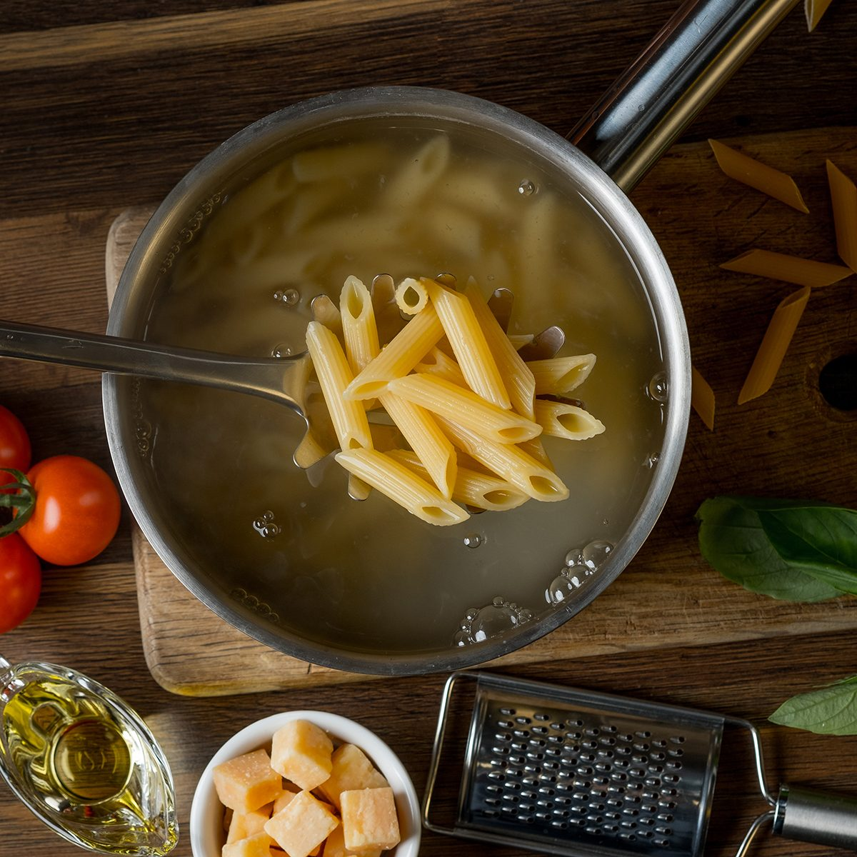 Home cooking pasta in a saucepan with water and cooking ingredients with a cutting board on the background of a wooden table,