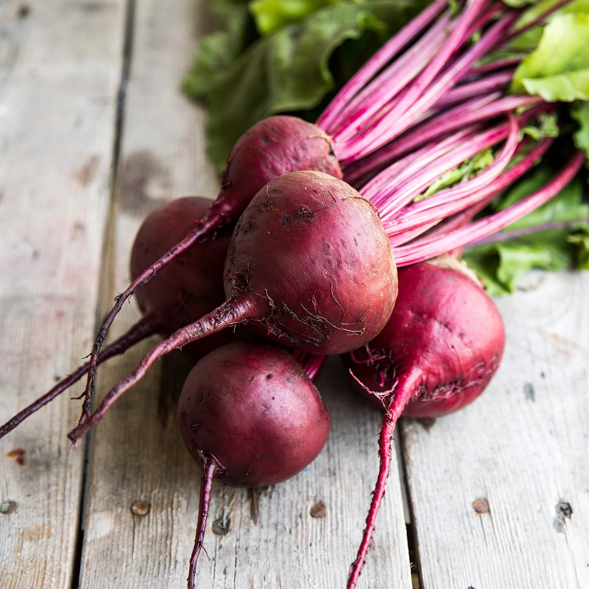Red Beetroot with herbage green leaves on rustic background.