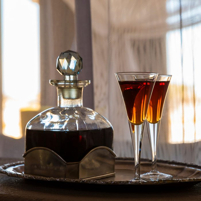Two glasses an a carafe filled with red sherry in a room with a lot of sun