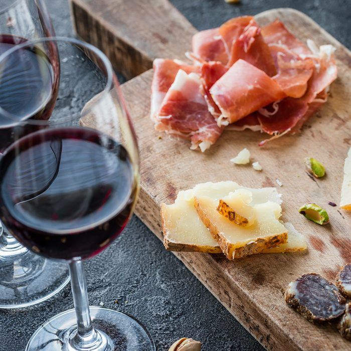 Platter with Spanish ham jamon serrano or Italian prosciutto crudo, sliced Italian hard cheese pecorino toscano, homemade dried meat salami, glasses of red wine and pistachios, on old wooden board