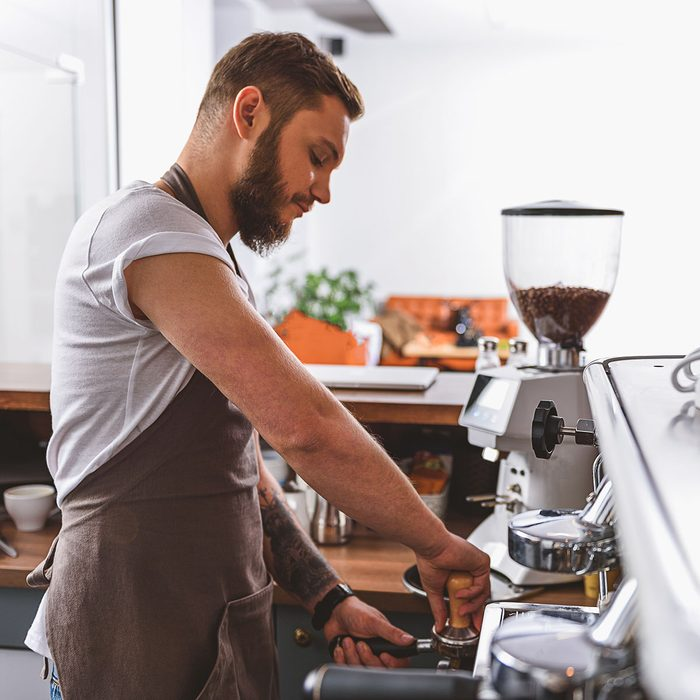 bearded barista tamping ground coffee