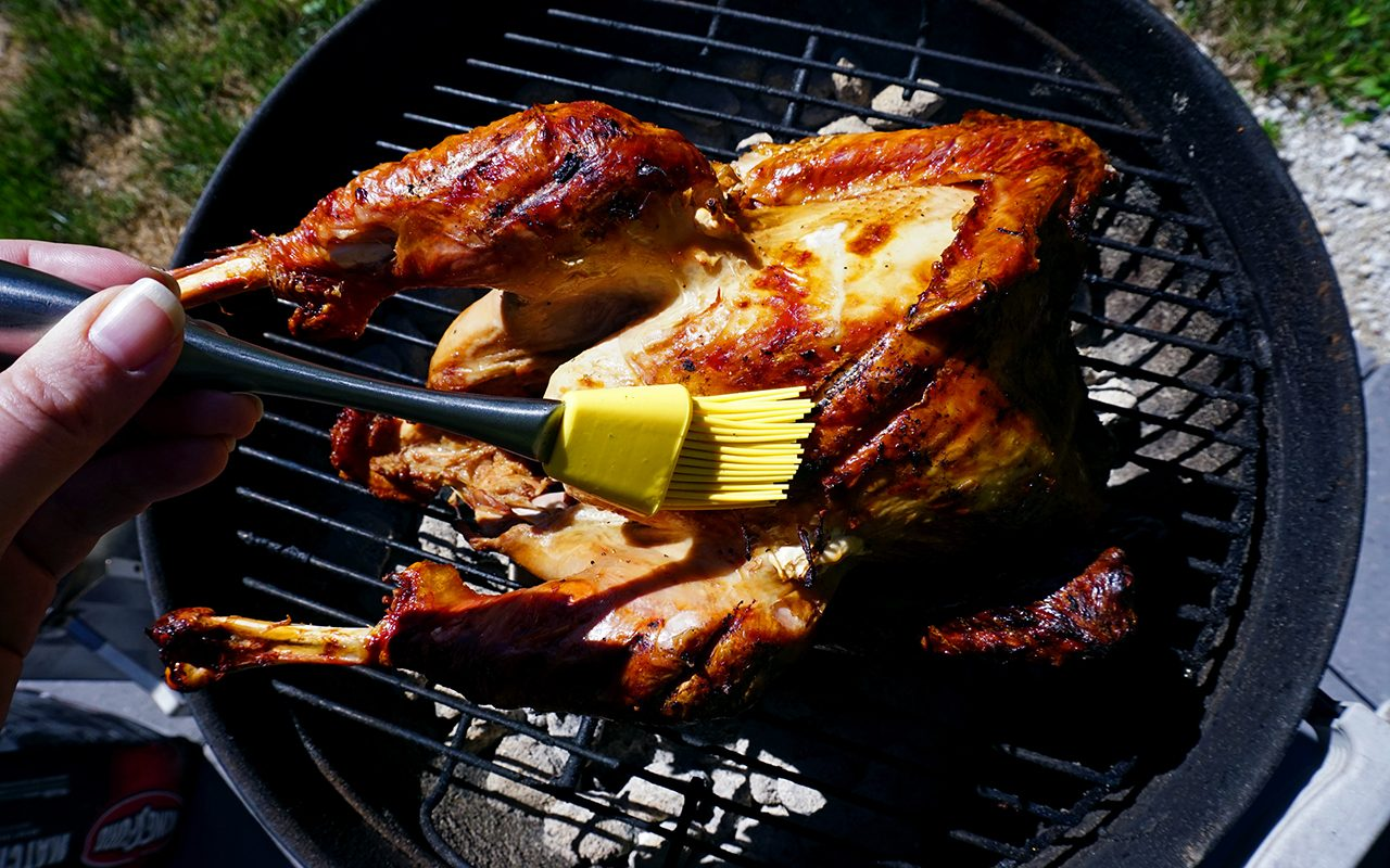 basting the grilled turkey with reserved marinde