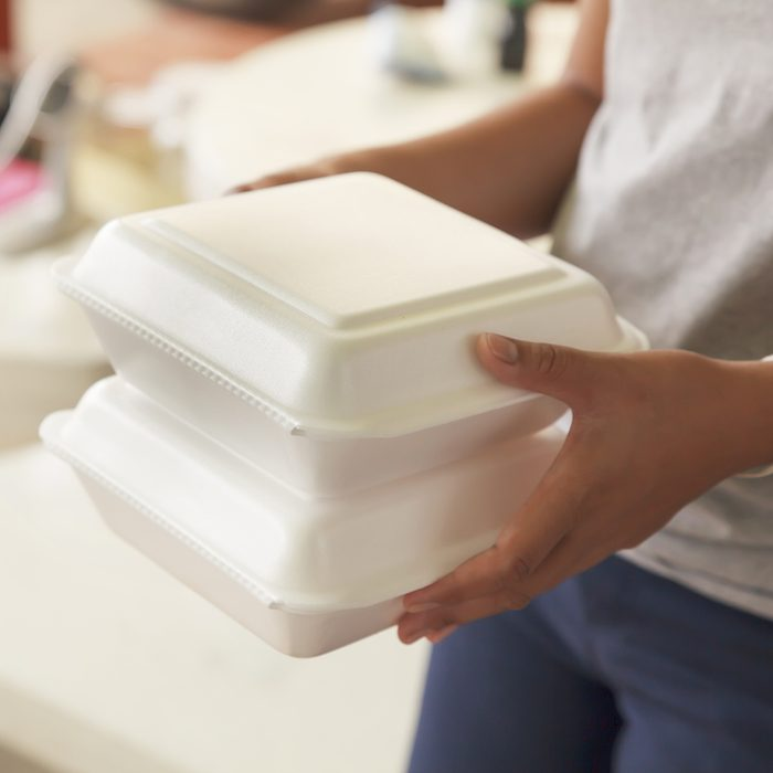 Hand holding foam boxes rice.