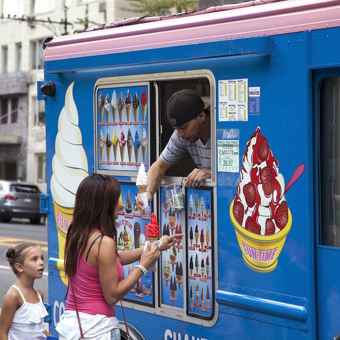 Man sells soft ice cream cone to customers on Columbus Circle.