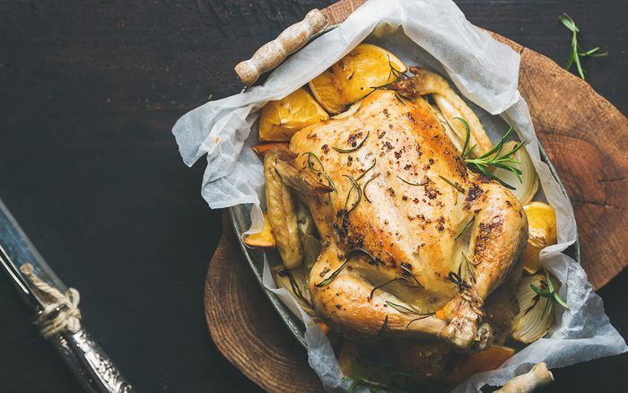 Roasted whole chicken stuffed with oranges, bulgur and rosemary on wooden board