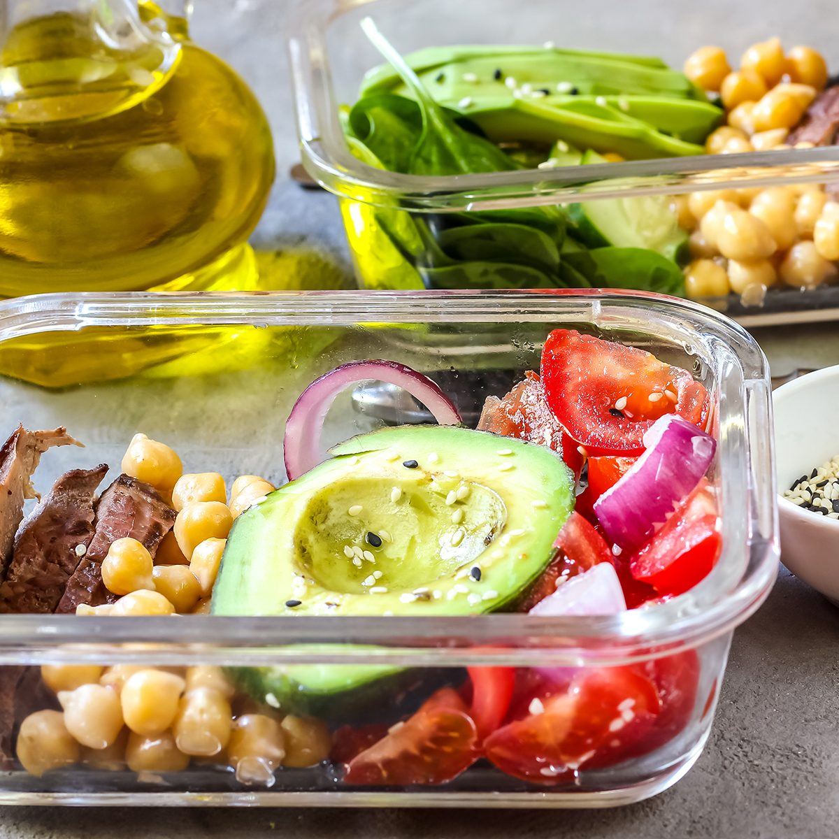 Healthy meal prep containers with chickpeas, goose meat , tomatoes, avocado, lemon and spinach. Top view; Shutterstock ID 1081277720