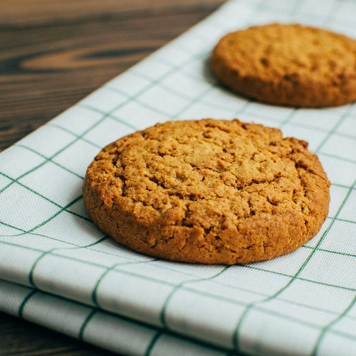 Close-up three tasty oatmeal cookies laying at the green checkered textile kitchen towel at wooden surface of bakery, cafe or kitchen table in the morning during the breakfest in cozy atmosphere