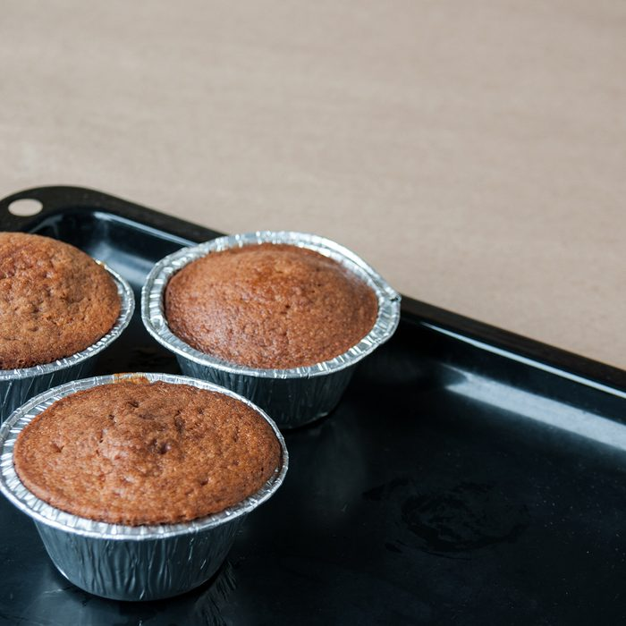 Fresh cupcakes are on a black pan on the table, cookie sheet, cupcake