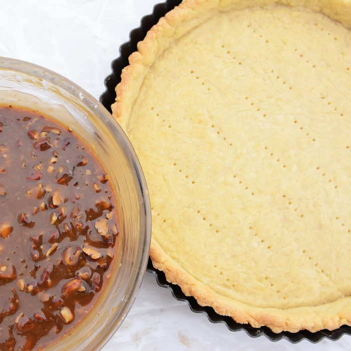 Making pecan pie - nutty pie filling ready to pour into the blind-baked pie crust; Shutterstock ID 311205740; Job (TFH, TOH, RD, BNB, CWM, CM): Taste of Home