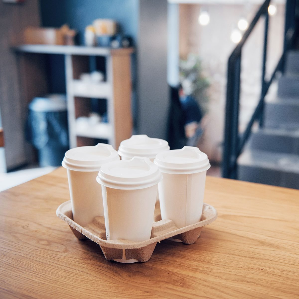 Take coffee to work for the entire office. High angle shot of a cardboard take out tray with four coffee cups with lids.