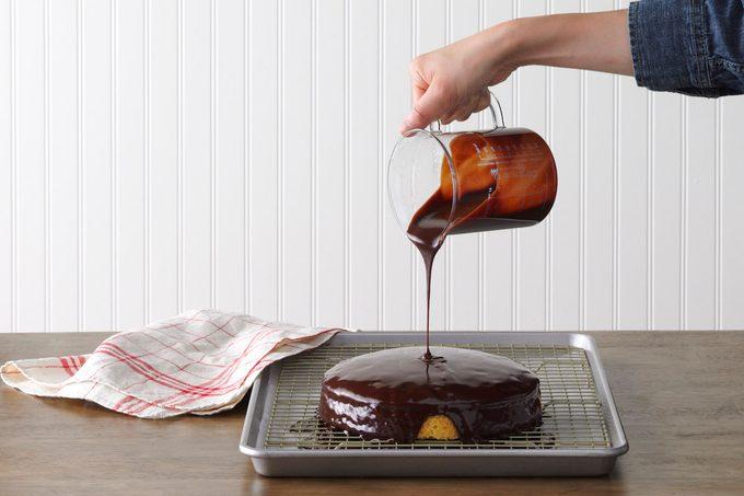 A person pouring homemade chocolate ganache over a cake.