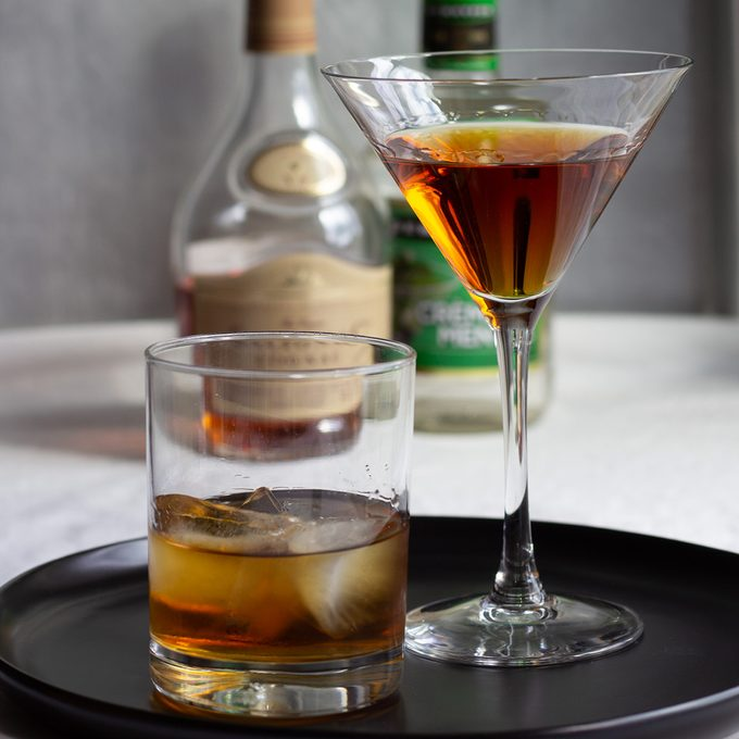 Stinger cocktail two ways - in a cocktail glass and on the rocks, with cognac and creme de menthe in background.